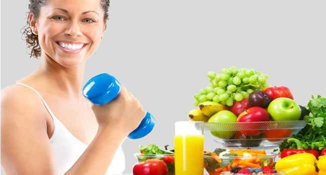 Mulher-ao-lado-de-alimentos-saudáveis-segurando-um-peso-de-academia